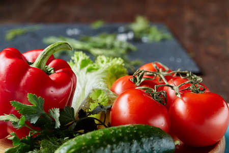 Close-up still life of assorted fresh vegetables and herbs on dark wooden background, top view, shallow depth of field.