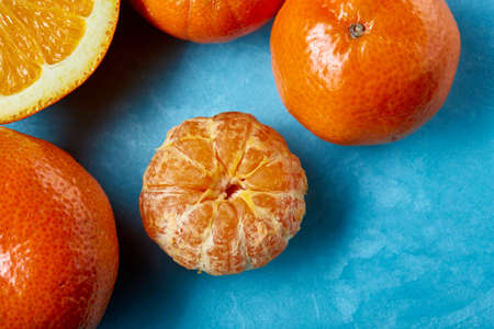 Variety of fresh citrus fruits for making juice or smoothie over blue textured background, top view, selective focus.