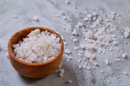 Large white sea salt crystals in a natural wooden bowl on white textured background, top view, close-up, selective focus, shallow depth of field. Spa natural concept. Dayspa cosmetics products. Spa and wellness setting.