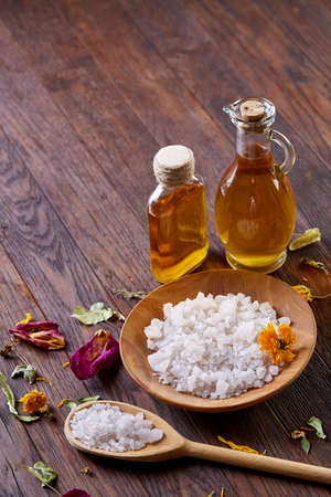 SPA concept: composition of spa treatment with natural sea salt, aromatic oil and flowers on wooden background, close up, top view, selective focus, shallow depth of field. Dayspa cosmetics products. Spa natural concept. Spa and wellness setting.
