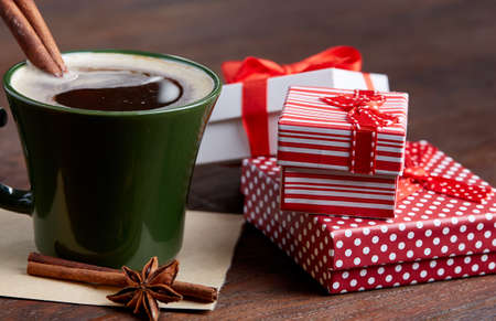 Still life with cup of coffee holiday gift in small red color box with ribbon and bow on wooden background, top view, close-up