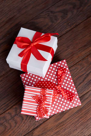 Still life with holiday gift in small red color box with ribbon and bow on wooden background, top view, close-up Stock fotó