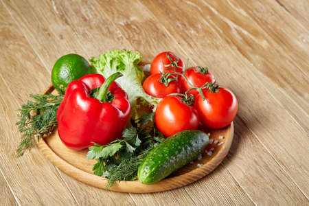 Close-up still life of assorted fresh vegetables and herbs on vintage wooden background, top view, selective focus. Stock Photo