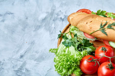 Fresh sandwich with lettuce, tomatoes and cheese served on wooden plate over white textured background, selective focus