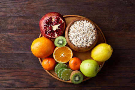 Bowl with oatmeal flakes served with fruits on wooden tray wooden background, flat lay, selective focus