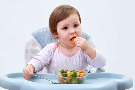 Adorable toddler girl is having fun while eating stewed vegetables on white background Stock fotó