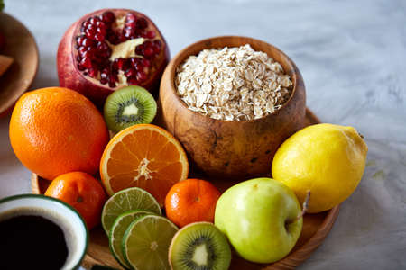 Bowl with oatmeal flakes served with fruits on wooden tray over rustic background, flat lay, selective focus Stock Photo