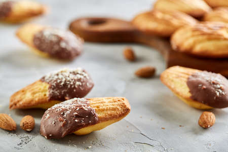 Homemade pastry. Almond cookies and raw almonds on wooden cutting board over white textured background, close-up, selective focus, shallow depth of field. Delicious homemade biscuits. Amaretto biscotti. Yummy confectionary. Food concept. Stock Photo