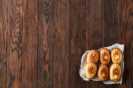 Sweet almond cookies arranged in rows on white piece of paper over vintage wooden background, close-up, selective focus. Delicious homemade biscuits. Amaretto biscotti. Yummy confectionary. Food concept. Stock Photo