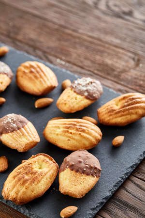Freshly baked almond cookies on stone board over vintage wooden background, top view, selective focus, shallow depth of field, vertical. Delicious homemade biscuits. Amaretto biscotti. Yummy confectionary. Food concept.