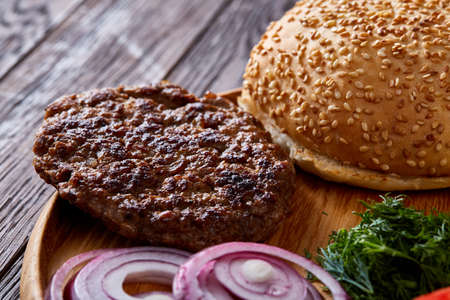 Yummy hamburger ingredients artistically organized on wooden plate over rustic vintage background, close-up, top view, shallow depth of field. Tasty snack on wooden table. Delicious fastfood. American cuisine. Colorful takeaway. Food background. Stock Photo