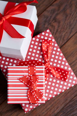 Still life with holiday gift in small red color box with pattern, covered with red ribbon and bow on rustic wooden background, top view, close-up, shallow depth of field, selective focus. Christmas background. Festive concept. Stock Photo