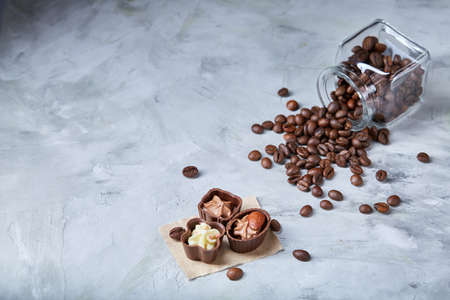 Side view of overturned transparent glass jar with roasted coffee beans and sweet chocolate candies over white textured background, selective focus, close-up. Delicious sweet starter. Tasty dessert. Food concept.