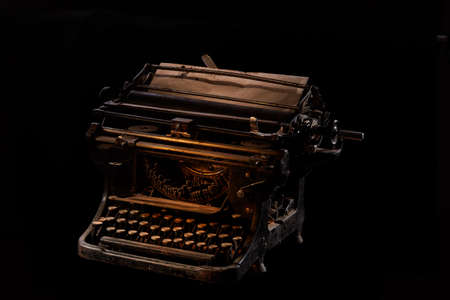 Concept picture of antique manual typewriter with vintage paper on black background, selective focus. Studio shot. Manuscripts doesnt burn. Artistic concept photo. Immortal art. Oldfashioned stylish object.