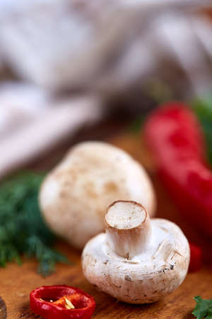 Composition of fresh hot pepper, mushrooms, dill and garlic on cutting board, plate with cooking salt over white textured background, close-up, selective focus. Ingredients ready to make salad. Delicious countryside still life. Food concept. Stock Photo