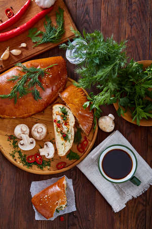 Countryside still life with delicious rustic pastries, cup of coffee, herbs and vegetables on a wooden cutting board over a vintage wooden background, selective focus. Yummy puffy meal. Tasty cobbler. Homemade appetizer.
