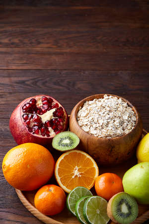 Bowl with oatmeal flakes served with kiwi, lime, lemon, orange, tangerin, apple and pomergranate on wooden tray over rustic wooden background, flat lay, selective focus. Healthy breakfast concept. Nutritious and diet snack. Stock Photo