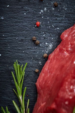 Raw meat beef steaks on black slate board with spices and rosemary over wooden background, copy space. Preparation for cooking. Hight quality barbeque. Gourmet beesteak. Organic protein. Nutritious butcher. Healthy food concept.