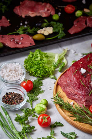 Still life of raw beef meat framed with tomatoes, garlic, brussels sprouts, dill, parsley, rosemary and spicies on wooden plate over vintage background, top view, selective focus. Preparation for cooking. Organic protein. Food concept.