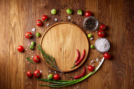 Various vegetables, seasoning cooking ingredients and salt with spicies around blank plate on light rustic wooden background, top view, selective focus, shallow depth of field. Healthy eating and diet food concept.