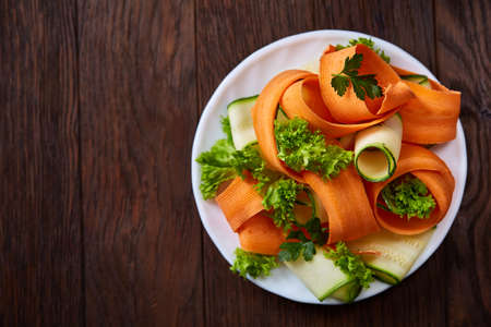 Artistically served vegetable salad with carrot, cucumber, letucce on white plate over wooden background, selective focus. Some copy space. Culinary masterpiece. Restaurant serving. Gourmet low fat dish. Healthy eating dieting.