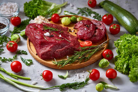 Still life of raw beef meat framed with tomatoes, garlic, brussels sprouts, dill, parsley, rosemary and spicies on wooden plate over white background, top view, selective focus. Preparation for cooking. Organic protein. Food concept.