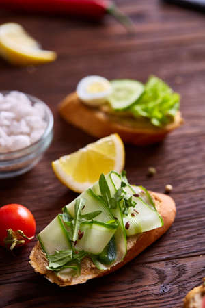 Breakfast sandwich with homemade paste, vegetables and fresh greens on rustic wooden background, shallow depth of field, close-up. Delicious morning appetizer. Gourmet bruschetta. Healthy eating concept.