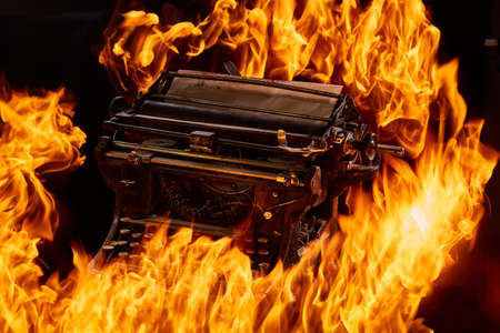 Concept picture of antique manual typewriter with paper burning on black background, selective focus. Studio shot. Manuscripts doesnt burn. Artistic concept photo with fire. Immortal art. Oldfashioned stylish object.