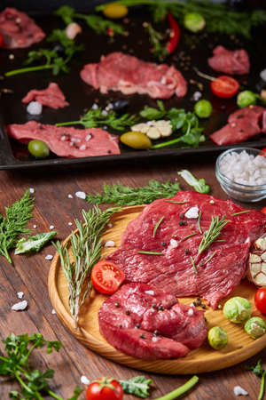Flat lay of raw beefsteak with tomatoes, garlic, hot pepper, dill, parsley, rosemary and spicies on metal cooking tray, close-up, selective focus. Preparation for cooking. Hight quality barbeque. Gourmet beesteak. Organic protein. Food concept.
