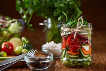 Delicious vegetable salad in jar, fresh veggies on cutting board, small sultanas with salt and spicies on table, selective focus, close-up, shallow depth of field. Preparation for cooking. Tasty homemade cuisine. Healthy organic eating. Food concept. Stock Photo