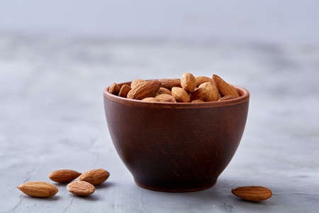 Wooden bowl of almonds on white textured background, top view, close-up, selective focus. Raw natural organic almond nuts. Healthy food for life. Some copy space. Uncooked protein. Natural oil source. Diet ingredient. Stock Photo