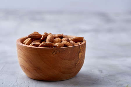 Wooden bowl of almonds on white textured background, top view, close-up, selective focus. Raw natural organic almond nuts. Healthy food for life. Some copy space. Uncooked protein. Natural oil source. Diet ingredient. Imagens