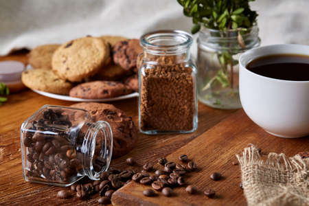 Conceptual composition with overturned glass jar of coffee beans, transparent bottle of instant coffee and tasty chocolate chip cookies on wooden table, selective focus, close-up, side view. Breakfast background. Food concept.