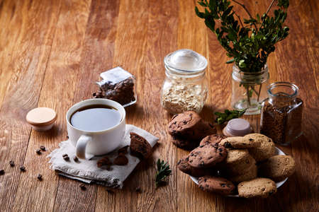 Breakfast still life with coffee cup on napkin, overturned jar with coffee beans, sweet cookies over rustic background, selective focus, close-up, top view. Delicious morning beverage. Time for calm and relax. Tasty dessert. Food concept.