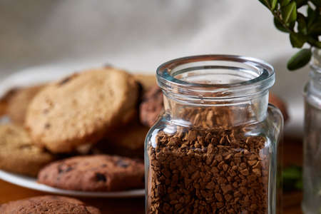 Open jar of instant coffee arranged on woden table, top view, close-up, selective focus, shallow depth of field. Rustic background. Studio shot. Delicious morning beverage. Food concept. Stock Photo