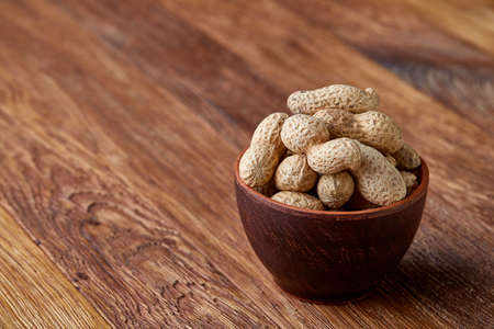 Unpeeled peanuts on a wooden background, top view, selective focus, shallow depth of field. Some copy space for your text. Studio shot. Organic nutritious ingredient. Gourmet appetizer. Tasty roast snack. Healthy food concept