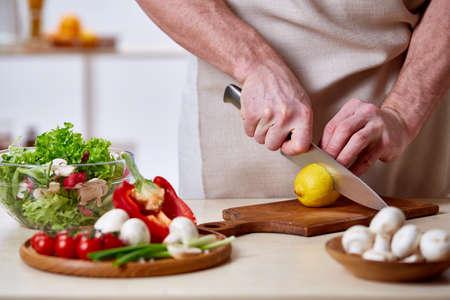 Man cooking at kitchen making healthy vegetable salad, close-up, selective focus. Variety of vegetables on wooden plate on white table in front of the chef. Skilful chef in an apron sqeezing lemon to the salad. Cooking and home concept Stock Photo