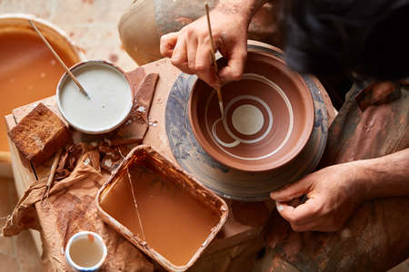 A potter in a plaid shirt and apron paints a clay plate in white in workshop, top view, close-up, selective focus. There are some tools, clay samples and paint jars in the background. Aristic manufacturing. Creative hobby. Art and crafts concept. Stock Photo