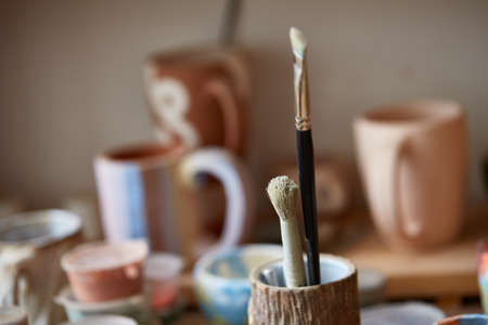 Close-up of various paint mugs and brushes in holder on worktop over wooden shelves with pottery, selective focus, side view. Preparing for decoration. Creative lay out. Handwork lifestyle. Handicraft concept