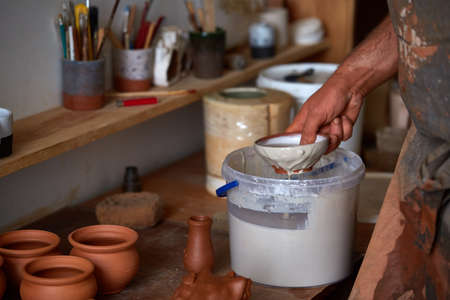 A potter in a plaid shirt and apron prepare paints to dye a clay plate in white in workshop, close-up, selective focus. Some tools, clay samples and paint jars in the background. Aristic manufacturing. Creative hobby. Art and crafts concept.