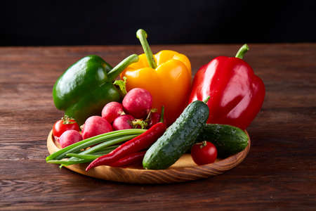 Wooden plate with vegetables for a vegetarian salad on rustic wooden background, close-up, selective focus. Cucumber, raddish, bell pepper and hot pepper ready to eat. Some copy space. Vegetable background. Food concept. Stock Photo