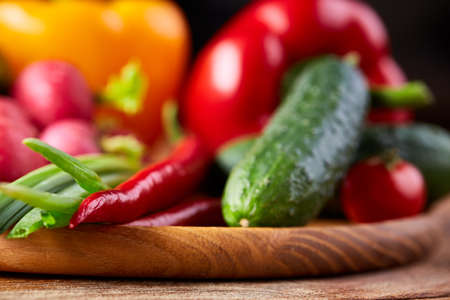 Vegetable composition of cucumber, tomatoes, and red and yellow bell pepper on flat plate on wooden table, close-up, selective focus. Studio shot. Vegetable background. Healthy food concept.