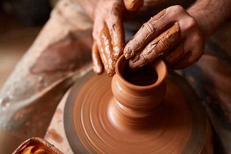 Mani del primo piano di un vasaio maschio in grembiule che fa un vaso da argilla, fuoco selettivo Archivio Fotografico