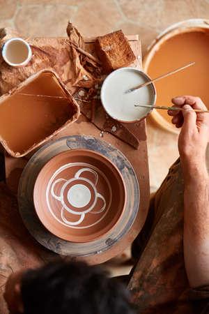 Scary face alike handmade potter mug on a wooden shelf, close-up, shellow depth of field.