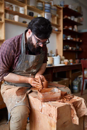 Portrait of a male potter in apron molds bowl from clay, selective focus, close-up Stok Fotoğraf
