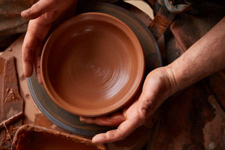 Close-up hands of a male potter in apron molds bowl from clay, selective focus Foto de archivo