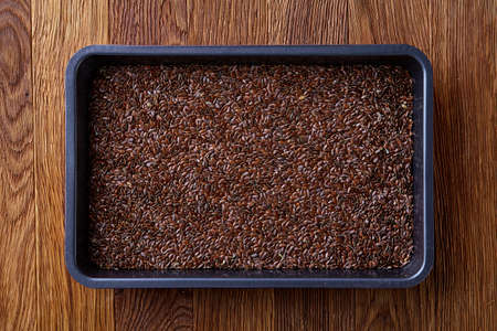 Nutritious flaxseed on baking tray over wooden background, selective focus, shallow depth of field. Nutritious and deitary ingredient. Natural organic condiment. Healing oilseed. Healthy lifestyle concept.