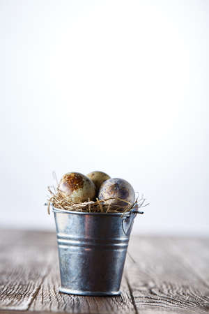 Small decorative bucket filled with quail eggs dark wooden table, close-up, selective focus, vertical. Stock Photo