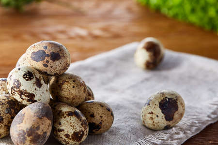 Quail eggs arranged in pyramid on a homespun napkin over a wooden table, close-up, selective focus. Conceptual Easter still life. Decorative rural composition. Healthy eating. Easter background. Healthy food concept. Zdjęcie Seryjne