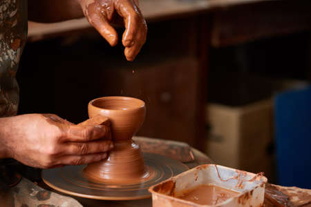 Close-up hands of a male potter in apron molds bowl from clay, selective focus Stock Photo